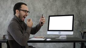 Hombre que comprueba sus dientes en la oficina cerca de la pantalla de ordenador Visualización blanca imagenes de archivo