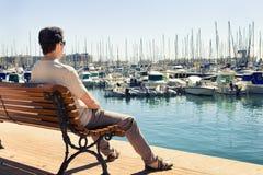 Hombre que comtempla los barcos en el puerto marítimo Fotografía de archivo