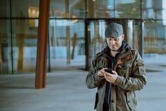 Hombre que comunica con su tel?fono m?vil en su vida urbana Concepto de la comunicaci?n, de la tecnolog?a y de la forma de vida foto de archivo libre de regalías