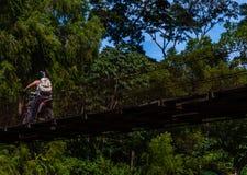 Hombre que conduce el montar a caballo sobre el puente viejo en montañas guatemaltecas imagen de archivo libre de regalías