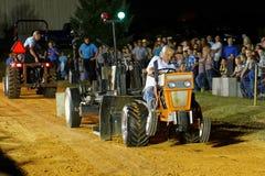 Hombre que conduce el tractor en la tracción de la competencia Fotos de archivo libres de regalías