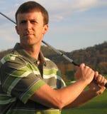 Hombre que conduce la pelota de golf en el tiempo de la te Foto de archivo libre de regalías