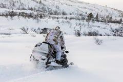 Hombre que conduce moto de nieve en la nieve Imagenes de archivo