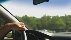 Hombre que conduce su coche Conducci?n del coche Naturaleza Mano masculina en cierre del volante para arriba resplandor 4k, cámar almacen de video