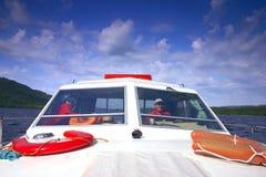 Hombre que conduce un barco en un asoleado Foto de archivo libre de regalías