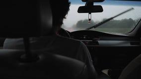 Hombre que conduce un coche bajo la lluvia en el agua de goteo del parabrisas almacen de video