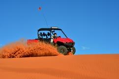 Hombre que conduce un coche de cuatro ruedas en la arena con el cielo azul Foto de archivo