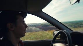 Hombre que conduce un coche en la opinión de la naturaleza de la forma de vida de los verdes del verano de las colinas de la vent almacen de metraje de vídeo