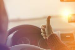 Hombre que conduce un coche en una carretera y que aumenta sus pulgares Día asoleado Foto de archivo