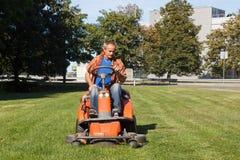 Hombre que conduce un cortacésped rojo (tractor) fotografía de archivo libre de regalías