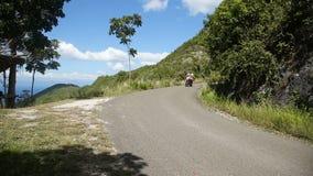 Hombre que conduce una motocicleta en el camino de la montaña metrajes