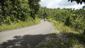 Hombre que conduce una motocicleta en el camino de la montaña almacen de video