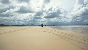 Hombre que conduce una motocicleta en la playa almacen de metraje de vídeo