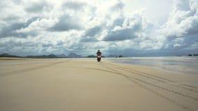 Hombre que conduce una motocicleta en la playa metrajes