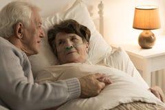 Hombre que conforta a la esposa enferma imagen de archivo libre de regalías