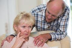 Hombre que conforta a la mujer mayor con la depresión Fotografía de archivo libre de regalías