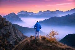 Hombre que considera en el valle de la montaña con las nubes bajas la puesta del sol colorida fotografía de archivo