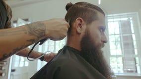 Hombre que consigue corte de pelo de moda en el salón almacen de video