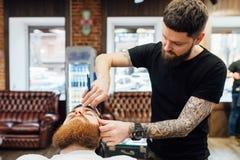 Hombre que consigue corte de pelo de moda en la peluquería de caballeros fotos de archivo libres de regalías