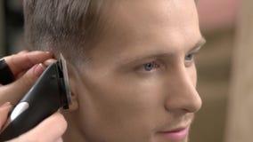 Hombre que consigue el corte de pelo, podadoras de pelo almacen de metraje de vídeo