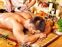 Hombre que consigue el masaje de piedra de la terapia. Imagen de archivo