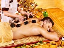 Hombre que consigue el masaje de piedra de la terapia. Foto de archivo libre de regalías