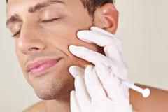 Hombre que consigue el tratamiento de la arruga cerca de boca imagen de archivo