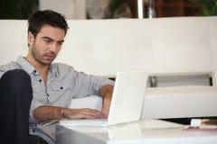 Hombre que controla sus email Imagenes de archivo