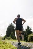 Hombre que corre abajo del camino al día soleado Imagenes de archivo
