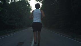 Hombre que corre afuera en naturaleza en la tarde lluviosa Corredor masculino que hace un funcionamiento en la oscuridad en una c metrajes