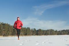 Hombre que corre al aire libre en día nevoso del invierno Foto de archivo libre de regalías