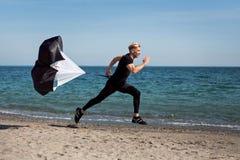 Hombre que corre con el paracaídas en la playa Fotografía de archivo libre de regalías