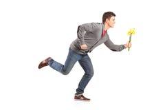 Hombre que corre con los tulipanes amarillos a disposición Imagen de archivo