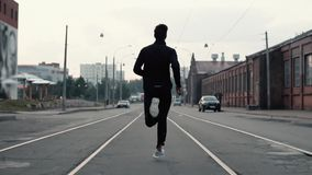 Hombre que corre en el medio de la calle Tiro del fondo Cámara lenta Concepto abstracto de éxito y de fama individuales almacen de metraje de vídeo
