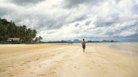 Hombre que corre en la playa almacen de video