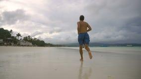 Hombre que corre en la playa metrajes