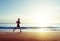 Hombre que corre en la playa tropical en la puesta del sol imagenes de archivo
