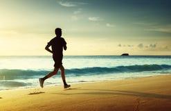 Hombre que corre en la playa tropical en la puesta del sol fotografía de archivo