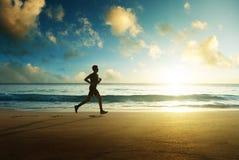 Hombre que corre en la playa tropical en la puesta del sol imágenes de archivo libres de regalías