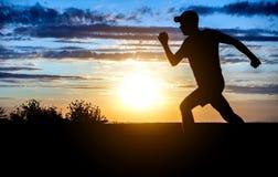 Hombre que corre en la puesta del sol Imagen de archivo libre de regalías