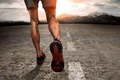 Hombre que corre en la puesta del sol Imagenes de archivo