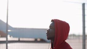 Hombre que corre en la puesta del sol en ciudad Corredor masculino afroamericano del atleta que lleva sudadera con capucha roja E metrajes