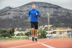 Hombre que corre en una pista corriente Foto de archivo