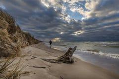 Hombre que corre en una playa en la puesta del sol Imagen de archivo libre de regalías
