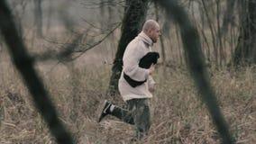 Hombre que corre lejos en el bosque almacen de video