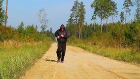 Hombre que corre a lo largo de la trayectoria de bosque almacen de video