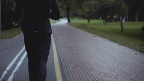 Hombre que corre a lo largo de un camino del parque Cámara lenta Visión posterior Custodia de ajuste del cuerpo Deportista que ac metrajes