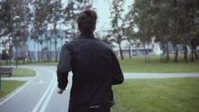 Hombre que corre a lo largo de un camino del parque de la ciudad Cámara lenta Visión posterior Inclinación para arriba Hombre de  almacen de metraje de vídeo