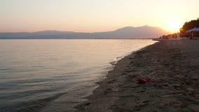 Hombre que corre a lo largo de una playa en la puesta del sol almacen de video