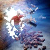 Hombre que corre a través de una pared de ladrillo fotos de archivo libres de regalías